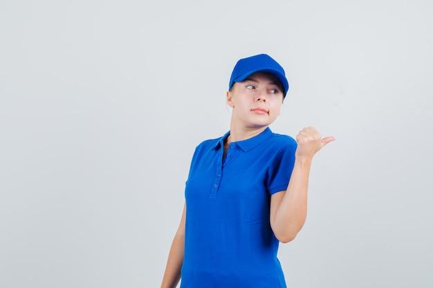 Kobieta dostawy wskazująca kciuk w niebieskiej koszulce i czapce i wyglądająca na niezadowoloną