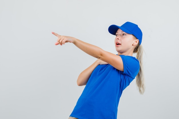 Kobieta dostawy wskazująca w niebieskiej koszulce i czapce i wyglądająca na zdumioną
