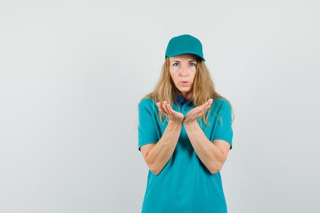 Kobieta dostawy wysyłająca pocałunek z nadętymi ustami w koszulce, czapce