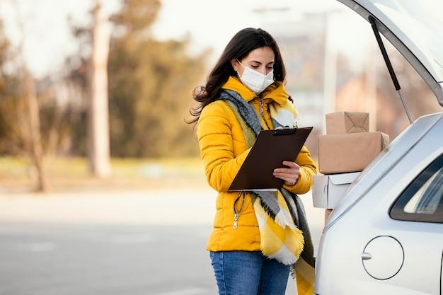 Kobieta dostawy z maską przewożącą pakiet