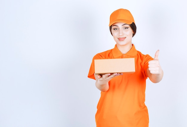 Kobieta dostawy z pudełkiem wskazującym kciukiem w górę