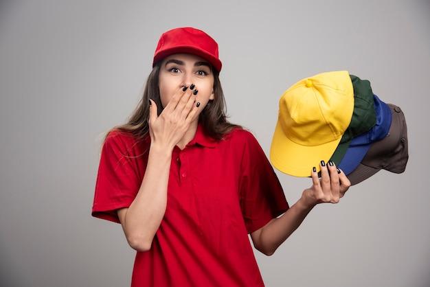 Kobieta dostawy zakrywających usta kolorowe czapki.