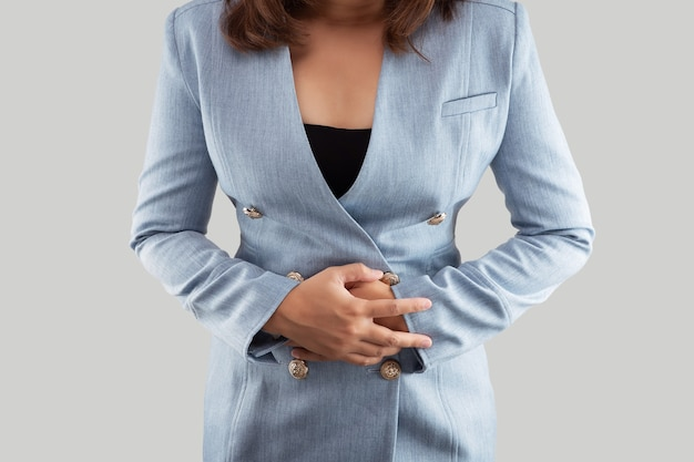 Kobieta dotyka bolesnego brzucha cierpiącego na skurcze miesiączkowe.