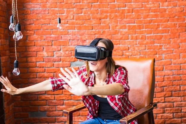 Kobieta dotyka czegoś za pomocą okularów wirtualnej rzeczywistości zestaw słuchawkowy.