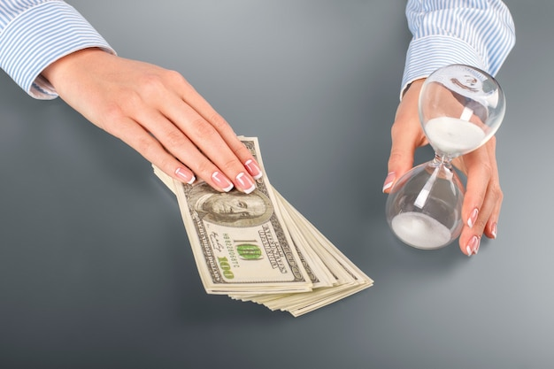 Kobieta dotyka dolarów i klepsydry. kobieta dotyka klepsydry i gotówki. pomyśl o swojej przyszłości. skoncentruj się i zdecyduj.