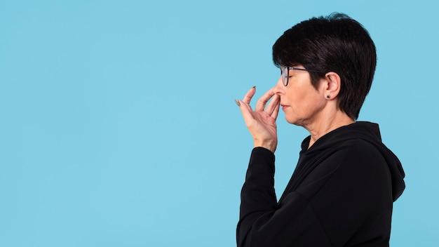 Kobieta dotyka jej nosa z miejsca na kopię