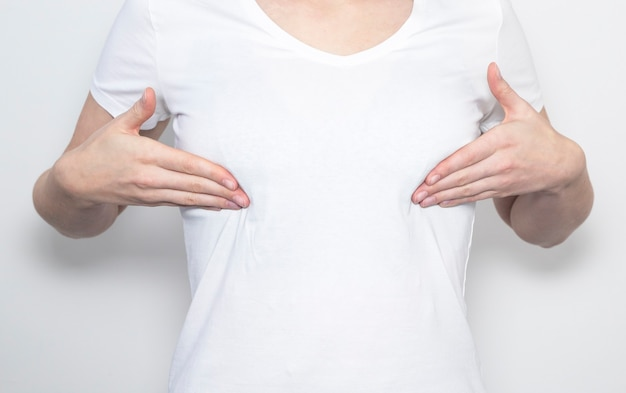 Kobieta dotyka jej piersi i bada siebie.