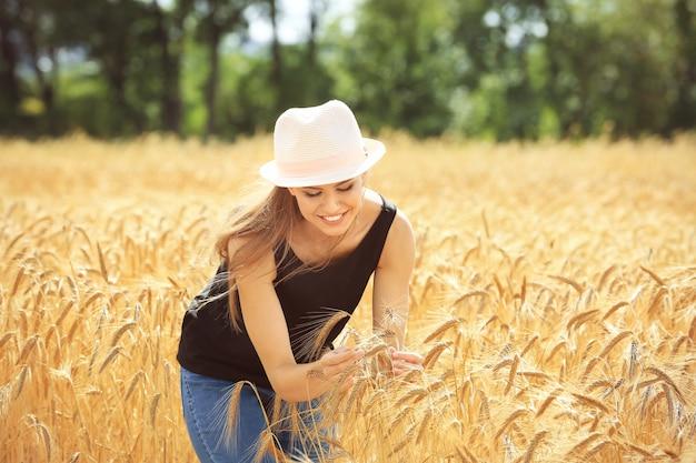 Kobieta dotyka kłosków pszenicy w polu