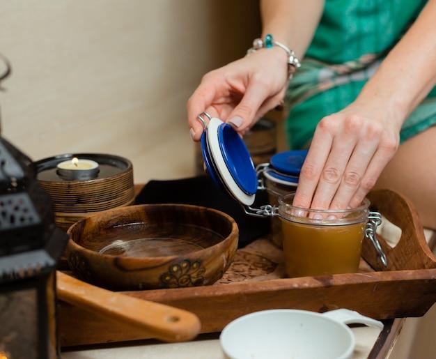 Kobieta dotyka miód pitny w słoiku