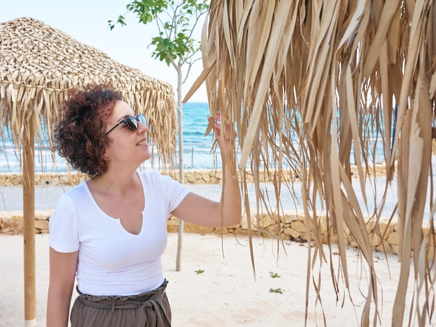 Kobieta dotyka palmowego parasola plażowego