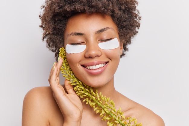 Kobieta dotyka twarzy czule trzyma oczy zamknięte trzyma roślinę nakłada pod oczy plastry upiększające, aby zmniejszyć zmarszczki na białym tle