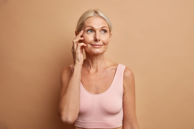 Kobieta dotyka twarzy ma zdrową skórę po zabiegach kosmetycznych lub zabiegach na twarz