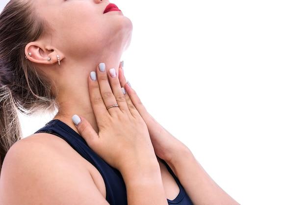 Kobieta dotykająca jej gardła na białym tle