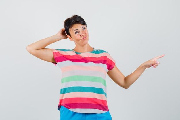 Kobieta drapiąca się po głowie, wskazująca na bok w t-shircie w paski i wyglądająca na wahającą się