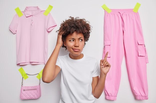 Kobieta drapie się głową w wiszące spodnie zastanawia się, w co się ubrać, prosi o radę, ubrana w swobodny t-shirt na białym tle