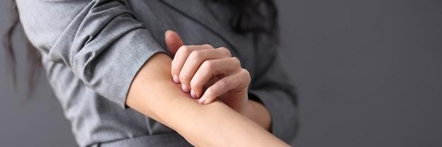 Kobieta drapie się w rękę manifestacją koncepcji nerwic