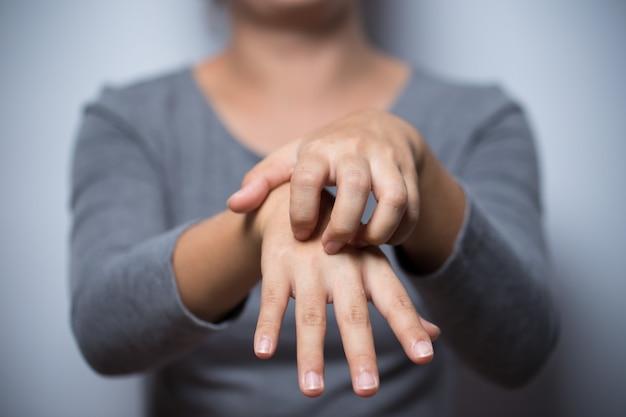 Kobieta drapie się w rękę