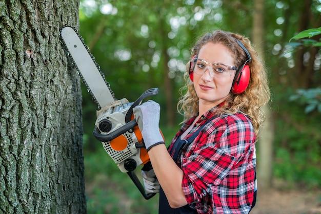 Kobieta drwal cięcia dębu z piłą łańcuchową w lesie