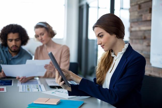 Kobieta dyrektor wykonawczy za pomocą cyfrowego tabletu w biurze
