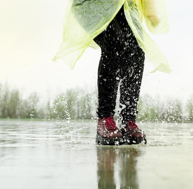 Kobieta działa na asfalcie w deszczową pogodę. zbliżenie na nogi i buty rozpryskiwania się w kałużach.