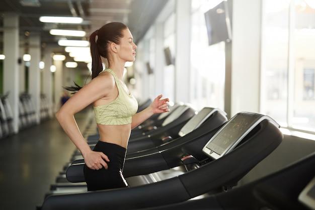 Kobieta działa na bieżni w siłowni