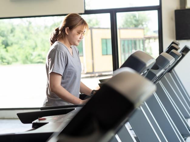 Kobieta działa na elektryczną karuzelę na siłowni fitness