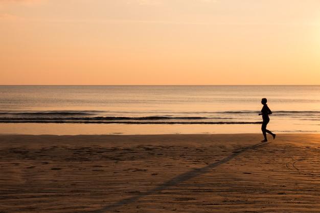 Kobieta działa na plaży o zachodzie słońca, zdrowy styl życia
