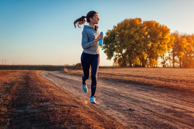 Kobieta działa trzymając butelkę wody w jesień pole o zachodzie słońca. pojęcie zdrowego stylu życia. aktywni sportowcy