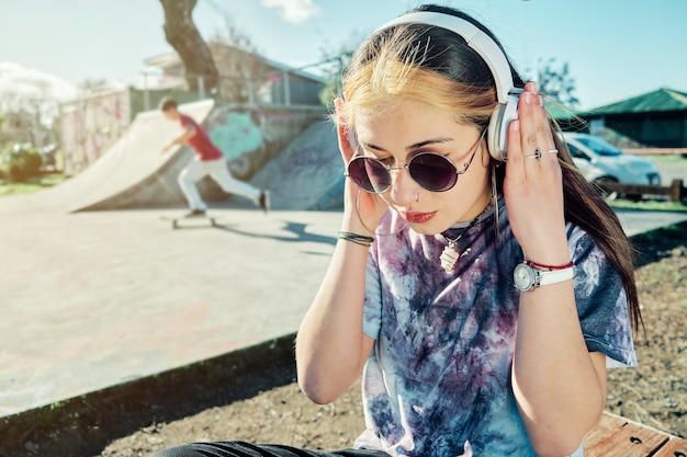 Kobieta dziewczyna na zewnątrz w parku, słuchanie muzyki na słuchawkach