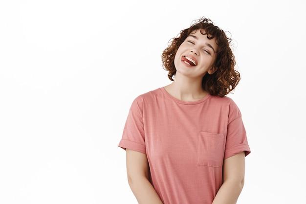 Kobieta, dziewczyna pokazuje język, uśmiecha się i śmieje, beztrosko przechyla głowę, cieszy się wakacjami, stoi pozytywnie na białym tle.
