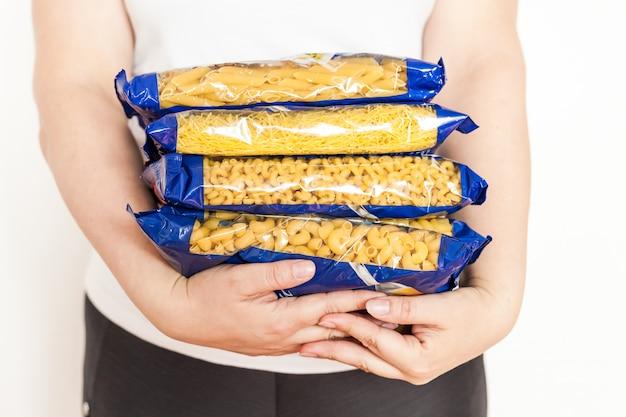 Kobieta, dziewczyna trzyma w wiązkach makaron, spaghetti, ravioli, produkty z ciasta, wywar