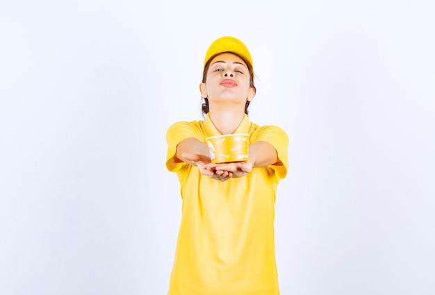 Kobieta dziewczyna w żółtym mundurze dostarczając klientowi żółty kubek z makaronem na wynos.