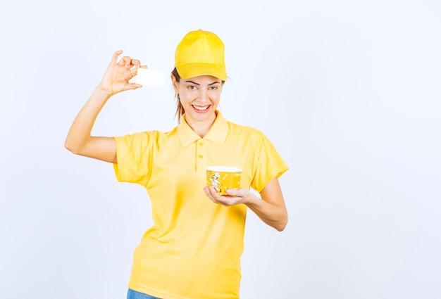 Kobieta dziewczyna w żółtym mundurze dostarczając żółtą filiżankę z makaronem na wynos i przedstawiając klientowi swoją wizytówkę.