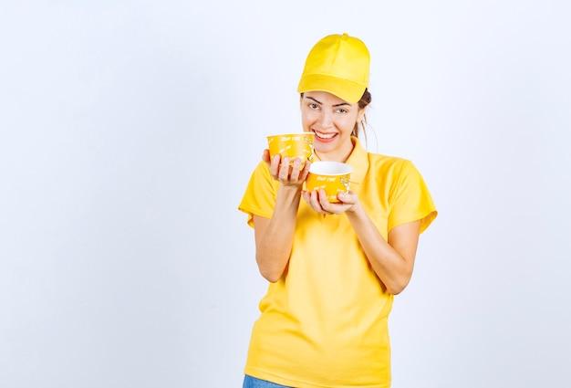 Kobieta dziewczyna w żółtym mundurze trzyma dwa kubki z makaronem na wynos.