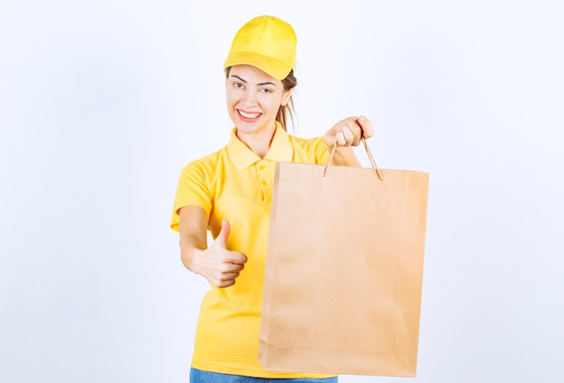 Kobieta dziewczyna w żółtym mundurze trzyma kartonową torbę na zakupy i pokazuje kciuk.