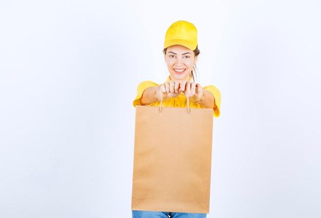 Kobieta dziewczyna w żółtym mundurze trzyma kartonową torbę na zakupy i prezentuje ją klientowi.