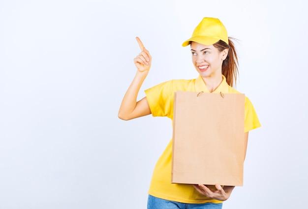Kobieta dziewczyna w żółtym mundurze trzyma kartonową torbę na zakupy i wskazuje gdzieś.