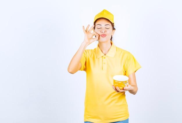 Kobieta dziewczyna w żółtym mundurze trzyma kubek z makaronem żółtym na wynos i pokazuje znak ręki przyjemności.