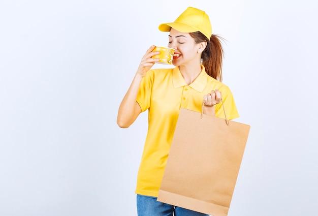 Kobieta dziewczyna w żółtym mundurze trzyma torbę na zakupy i pije zupę z makaronem na wynos.