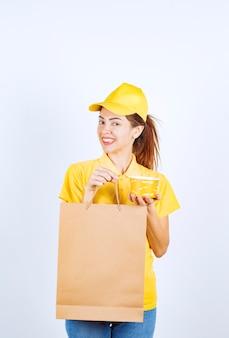 Kobieta dziewczyna w żółtym mundurze trzyma torbę na zakupy i żółty kubek makaronu na wynos.