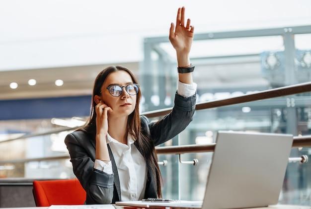 Kobieta dzwoni do kolegi, macha ręką na spotkanie. dziewczyna pracuje na laptopie w miejscu pracy.