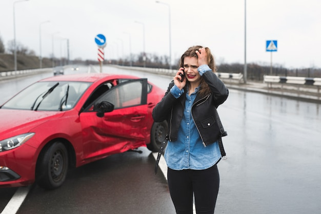 Kobieta dzwoni do serwisu stojącego przy czerwonym samochodzie