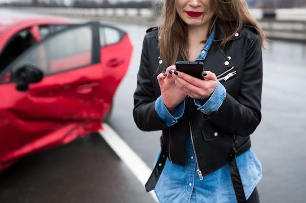 Kobieta dzwoni na służbę stojącą przy czerwonym samochodzie