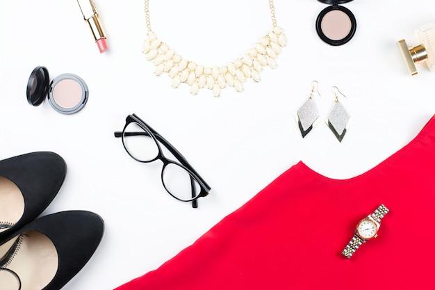 Kobieta elegancka czerwona sukienka, biżuteria, przedmioty do makijażu i czarne szpilki. leżał płasko