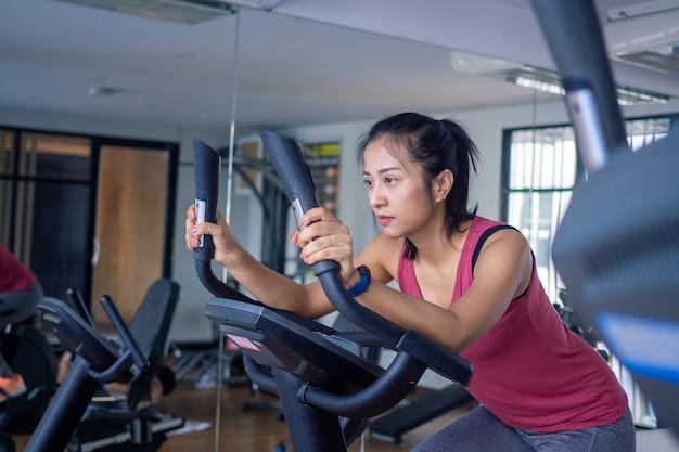 Kobieta elektryczni bicykle wewnątrz przy sprawności fizycznej gym. młoda kobieta treningu w siłowni zdrowy styl życia