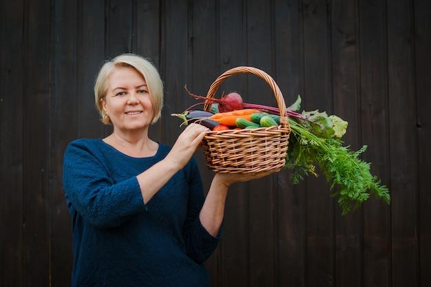 Kobieta emeryta rolnik trzyma kosz z organicznie warzywami uprawianymi w jej ogródzie.