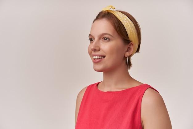 Kobieta emocja szczęśliwa zadowolona, uśmiechnięta i patrząc na bok ładną buzię z naturalnym makijażem i kolczykami, ubrana w stylową modną czerwoną sukienkę i żółtą bandanę na ścianie