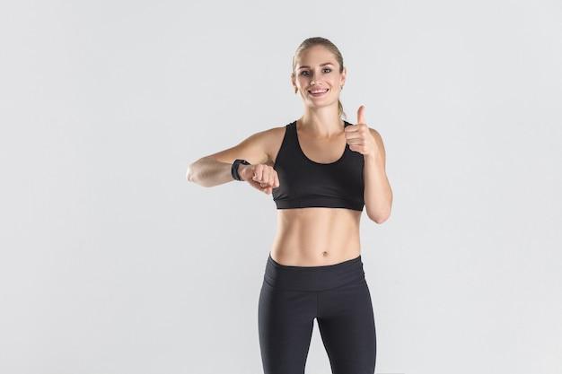 Kobieta energetyczna pokazująca kciuki w górę na strzał studio kamery