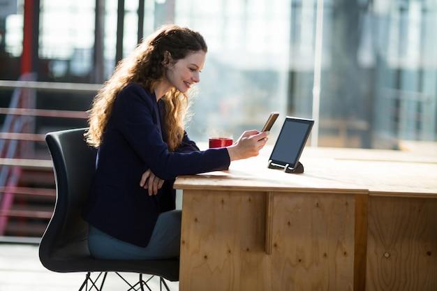 Kobieta executive business przy użyciu telefonu komórkowego przy biurku