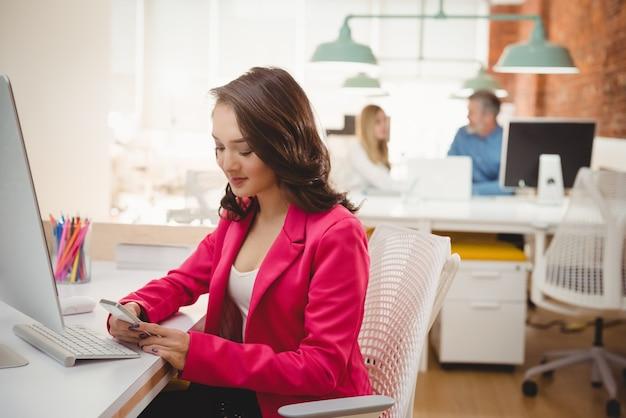 Kobieta executive przy użyciu telefonu komórkowego przy biurku